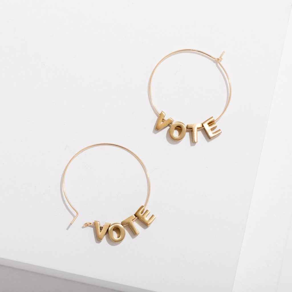 gold hoop earrings threaded with gold letters spelling the word vote