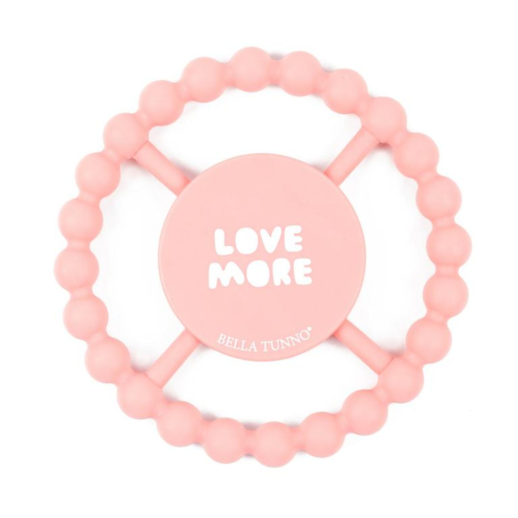 "pale pink teething ring with the words ""love more"" in white"