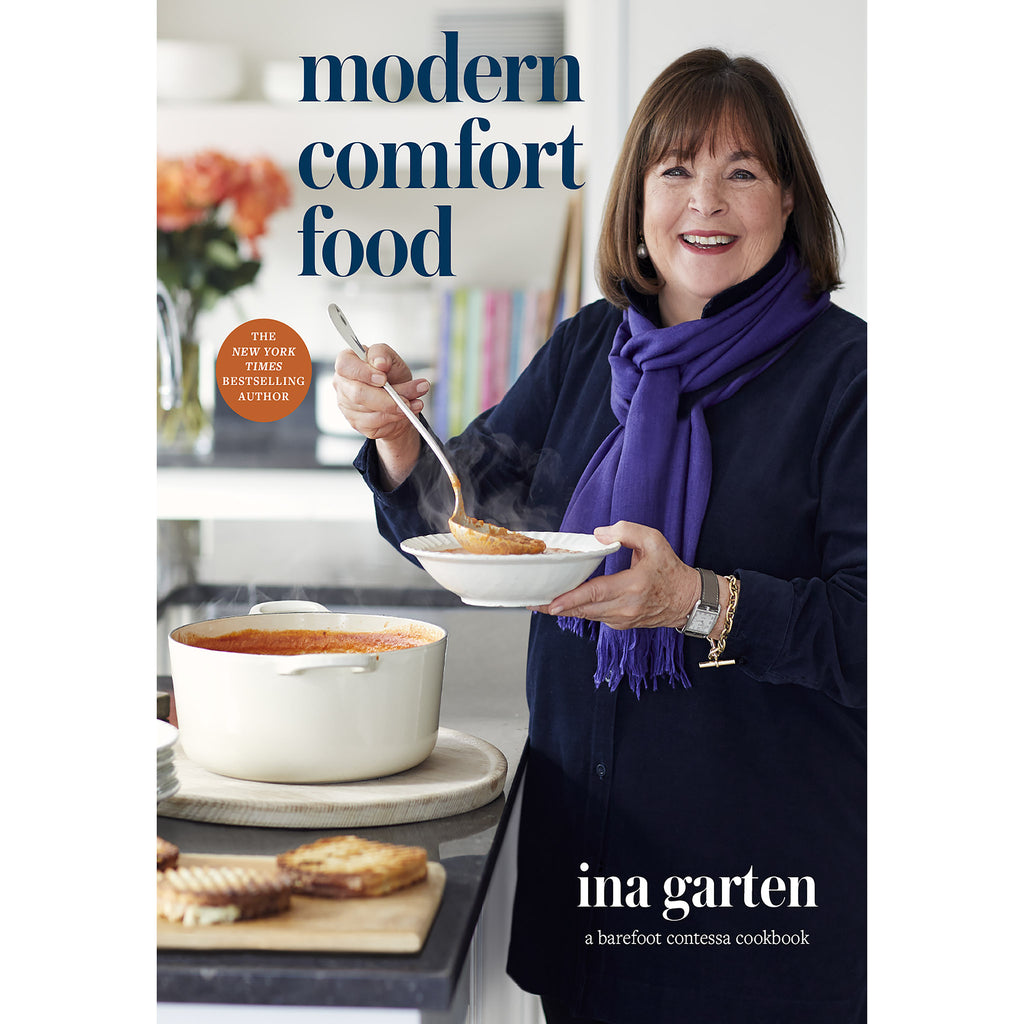 "cookbook cover with a photograph of ina garten serving a bowl of soup and the words ""modern comfort food"" in blue"