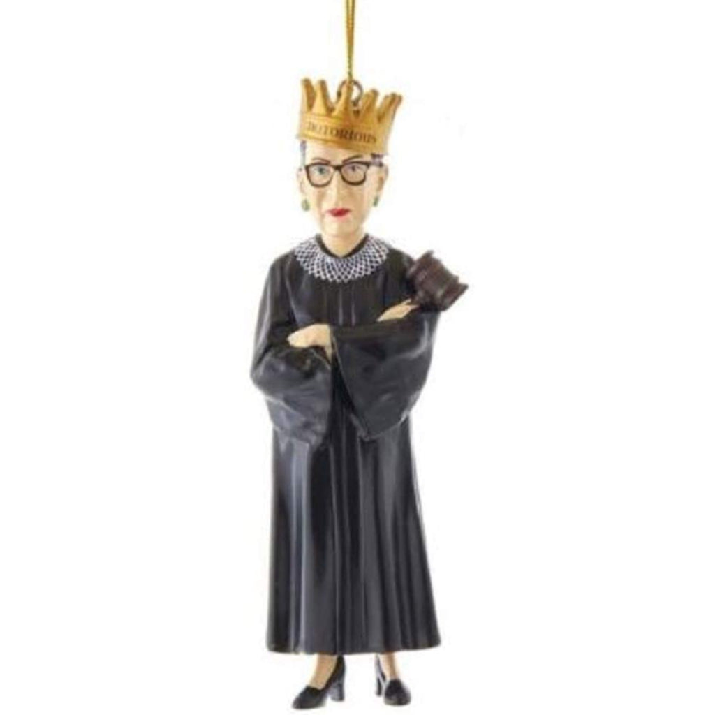resin ornament of ruth bader ginsburg standing in a lace collar and robe, holding a gavel, and wearing a crown with the word notorious