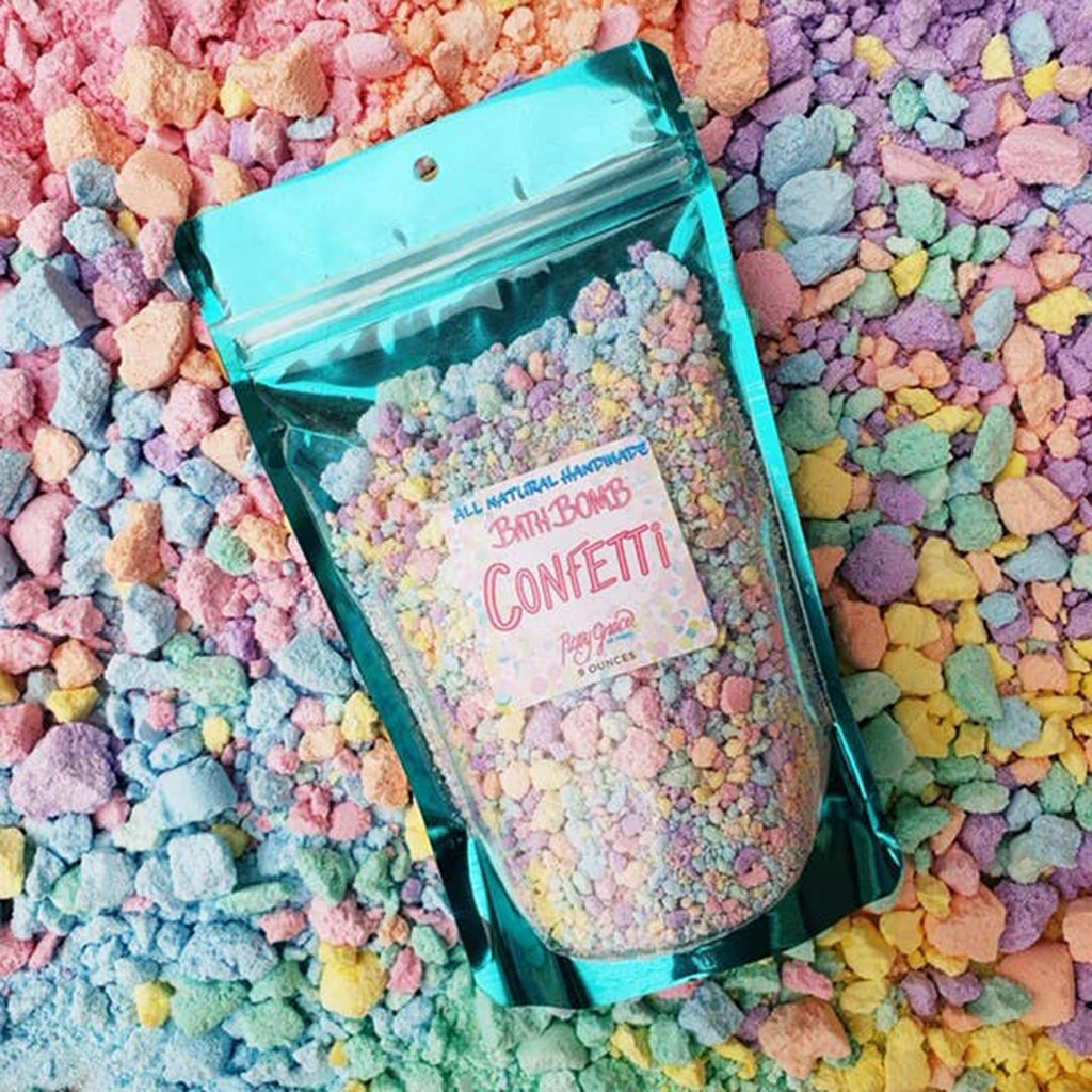 roxy grace all natural handmade scented bath bomb confetti in packaging on background of crushed bath bombs