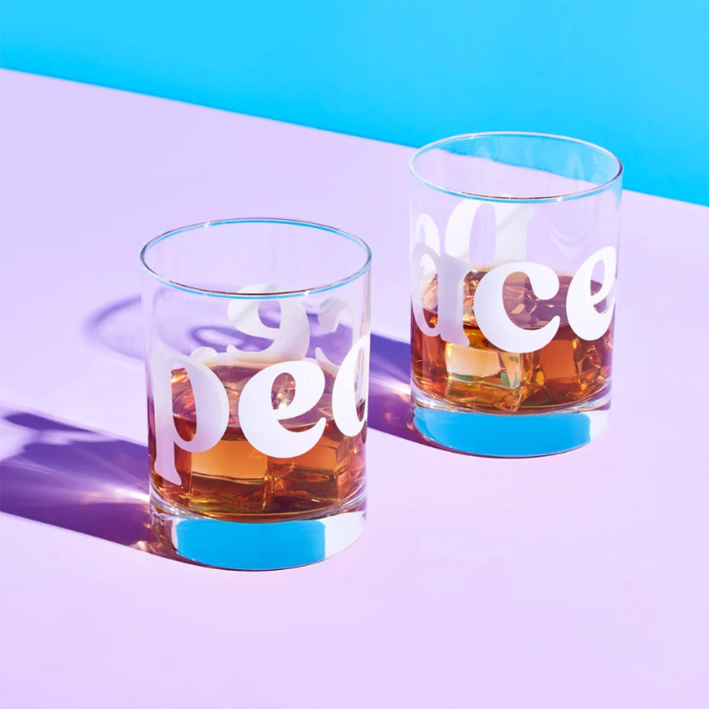 peace double old fashioned cocktail glasses on color background