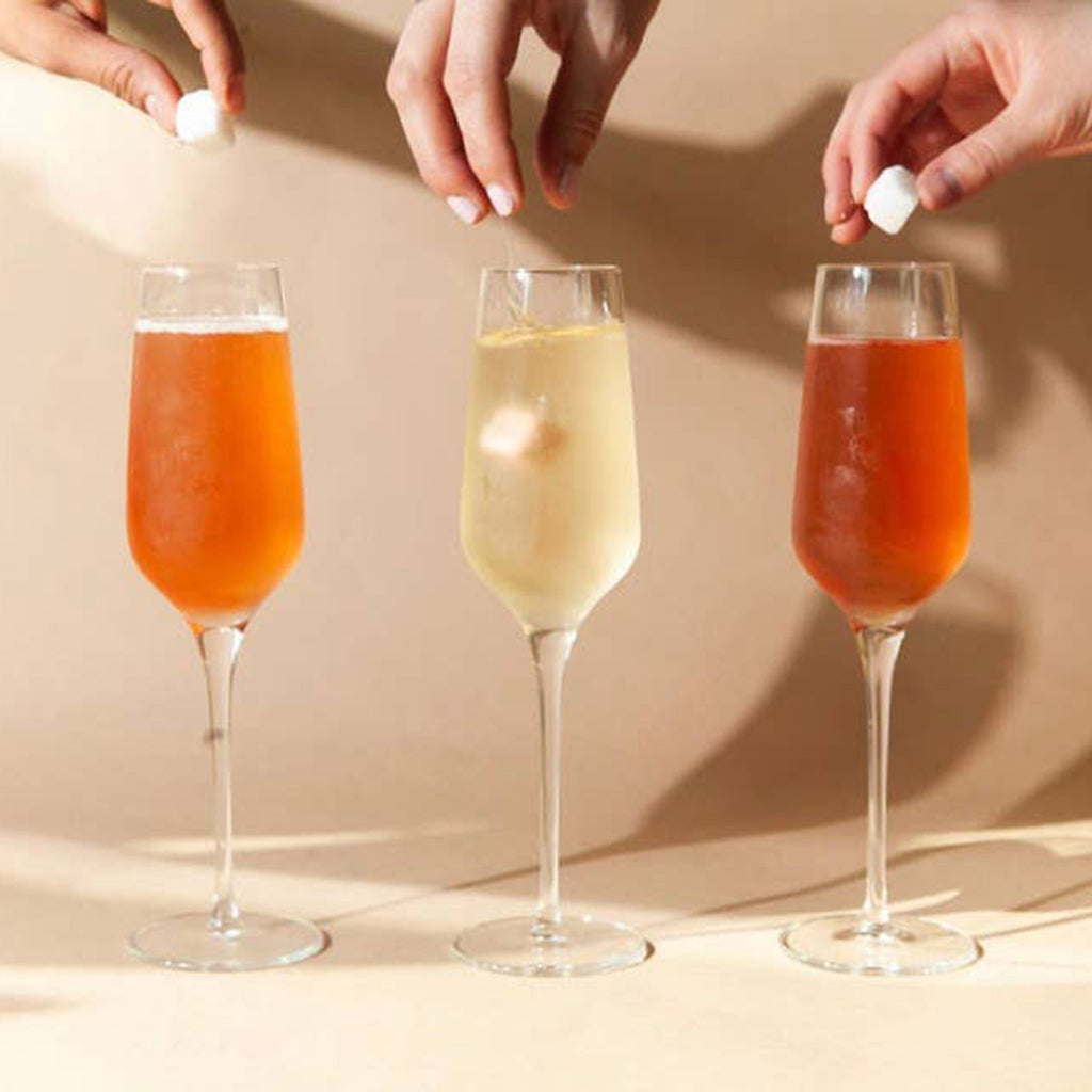teaspressa luxe bubblies citrus sugar set instant mimosa cocktail kit in use with champagne flutes