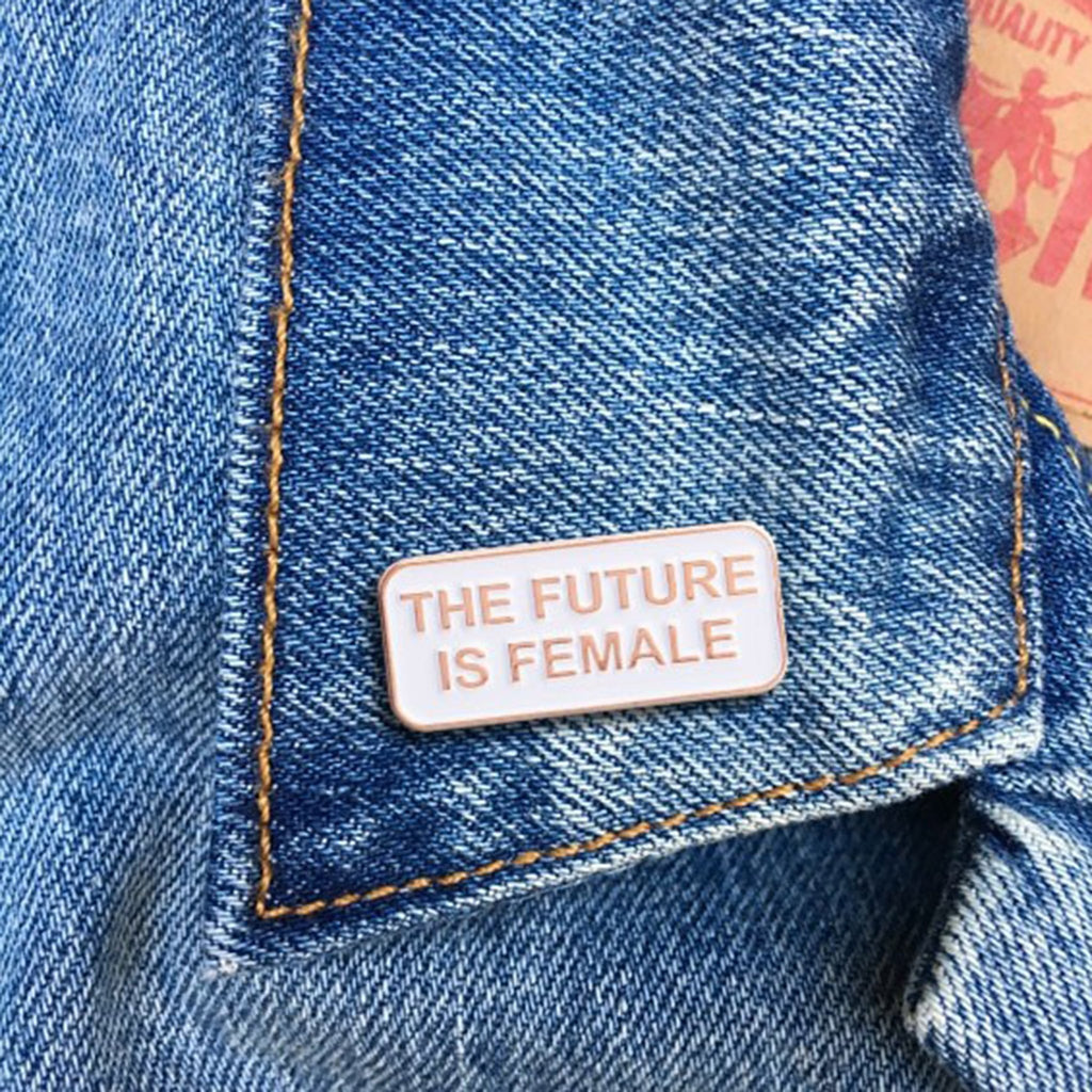 the found the future is female quote in rose gold on white enamel pin on denim jacket lapel