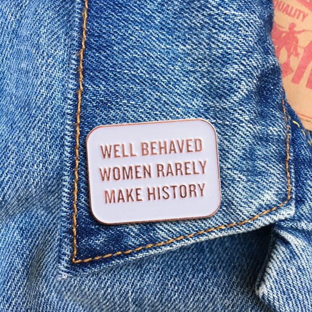 the found well behaved women rarely make history quote in rose gold on white enamel pin on denim jacket lapel