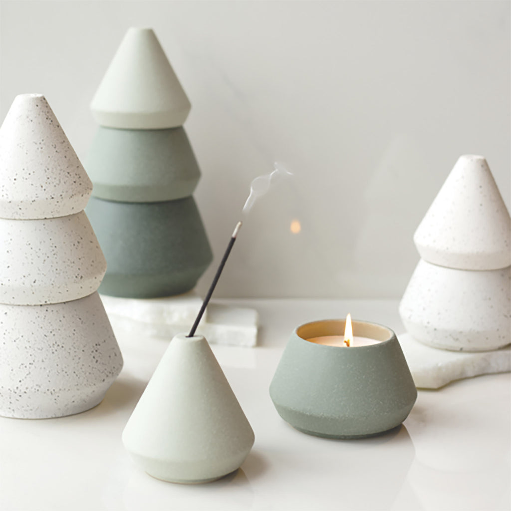 detail of ceramic stacking candle set showing a lit candle and incense in burner