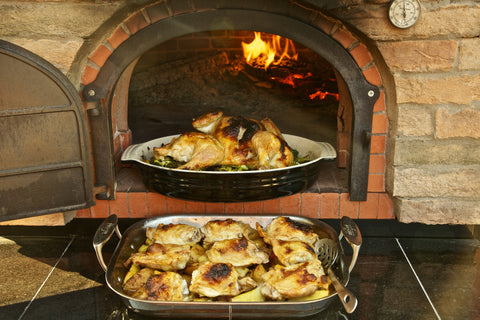 Chicken on a bed of vegetables made in a wood-fired oven