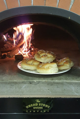 pretzels inside a wood fired oven with flames