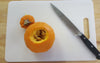 mini pumpkin with the top cut off knife and cutting board