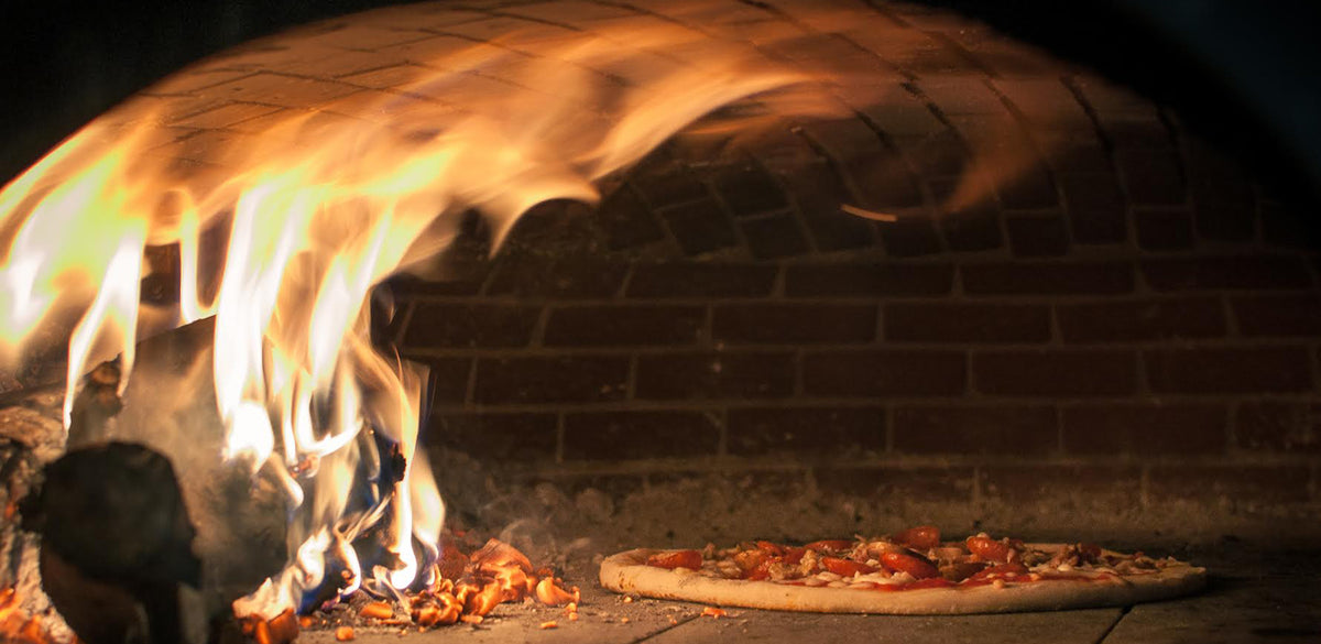 pizza cooking in a wood fired oven