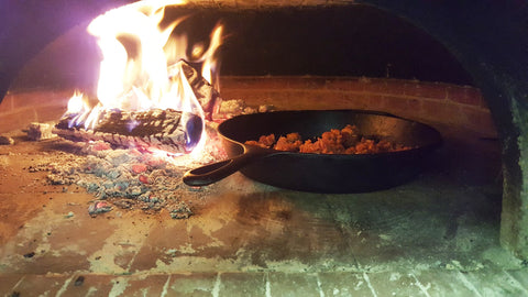 sausage cooking in a wood fired oven