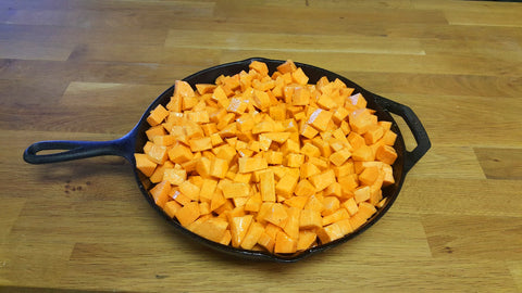raw sweet potatoes in an iron skillet