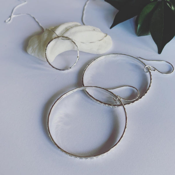 Textured silver hoop earrings on sterling silver ear hooks. These beauties are complete and serene.  Symbolising life's cycles and all that has no beginning and no end.  A beautiful symbol of the sacred geometry of life.  Handmade with love.  2.2mm solid sterling silver texture, in 4cm hoops.
