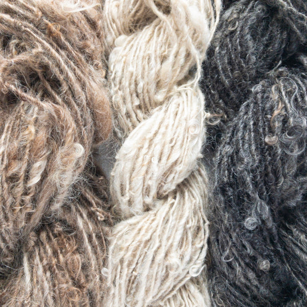 Closeup of three different handspun rusticspun 100% mohair yarn in white, brown, and black
