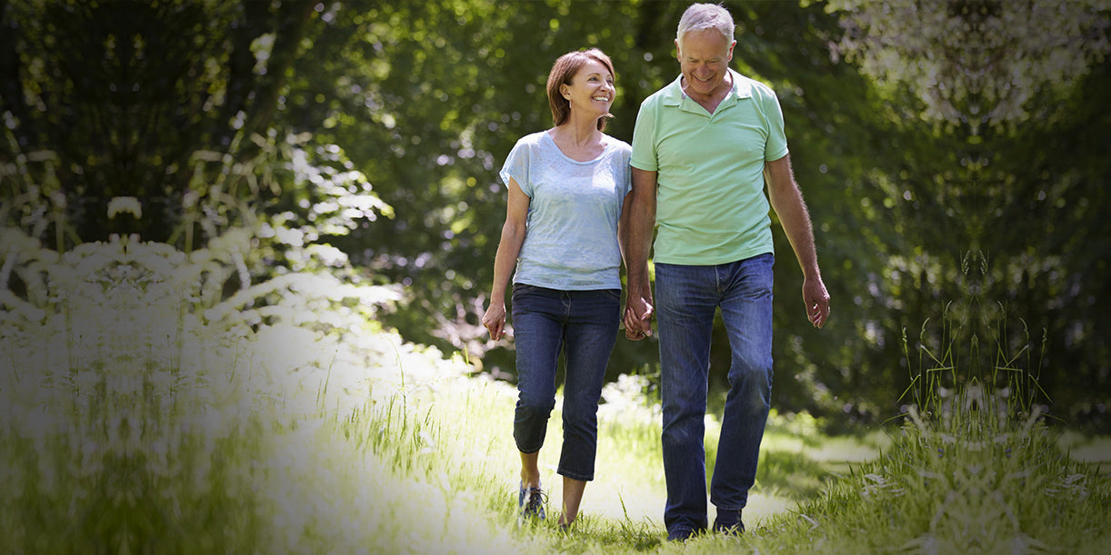 an older couple walk happily in the hiking trail