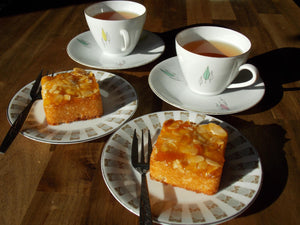 Coconutsquares on serving plates with tea - kokostaartjes - Big Bite Dutch Treats
