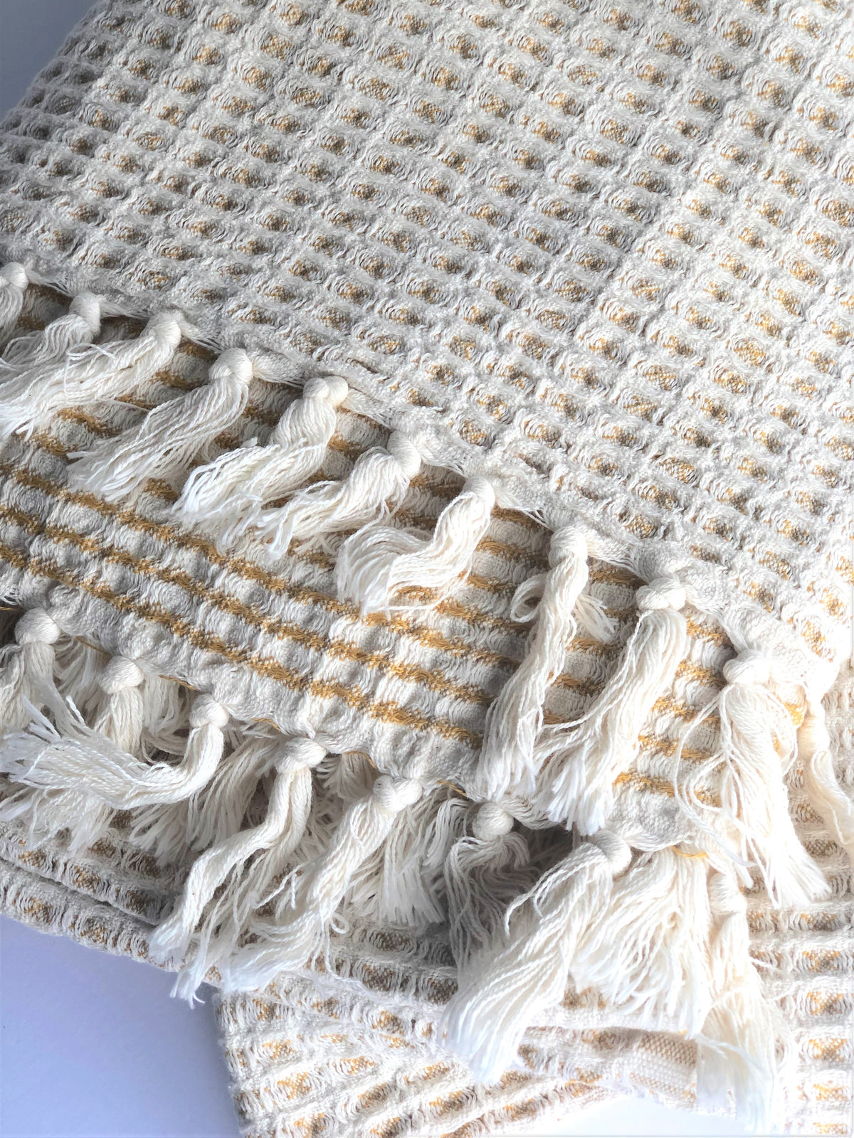 "the ""airloom"" throw in amber, with stripes on one side and natural undyed cotton with peeks of the striped color on the reverse"
