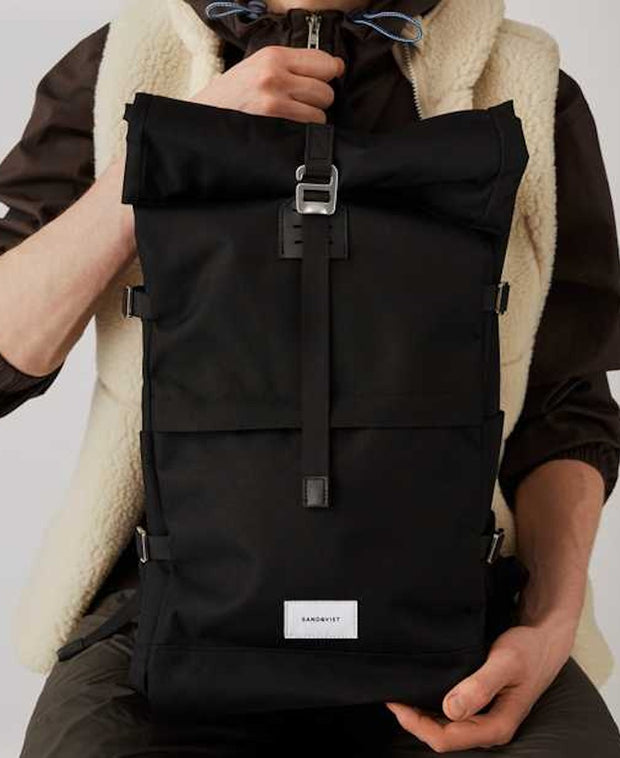 A guy holding a black rolltop backpack by Sandqvist of Sweden