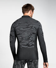Man wearing a patterned black half zip base layer by Odlo back view
