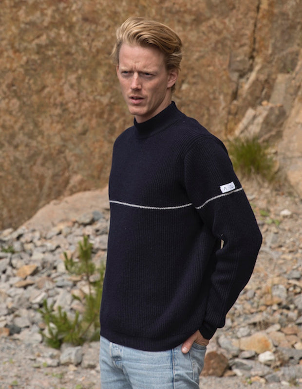 Blonde man wearing a blue striped Merino Sweater near rocks.