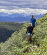 A couple hiking with the woman wearing LOng sleeve wool shirt for women by Norrona