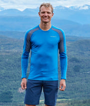 Man in the mountains wearing Long sleeve crew shirt in blue for men by Norrona