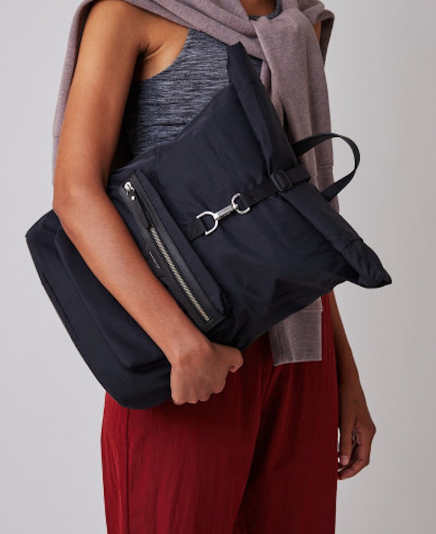 Woman cradling the new Black rolltop Siv Backpack by Sandqvist of Sweden