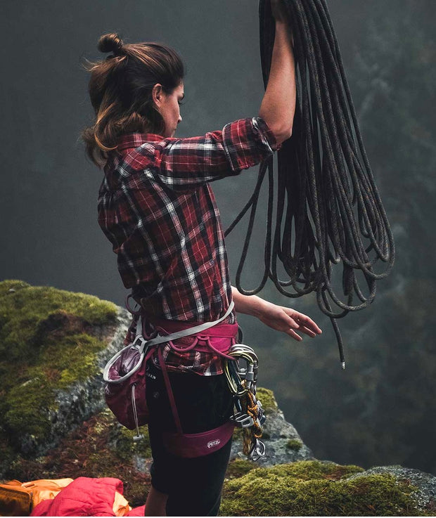 Woman rock climbing wearing the Skauen Field Shirt with the sleeves rolled up to her elbows