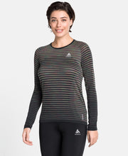 Woman wearing a black striped long sleeve running shirt by Odlo