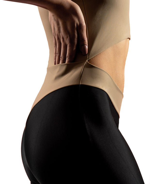 Side view of woman wearing sand VanillaShanti one-piece yoga bodysuit or unitard