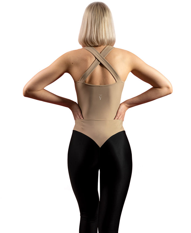 Back view of woman wearing sand VanillaShanti one-piece yoga bodysuit or unitard