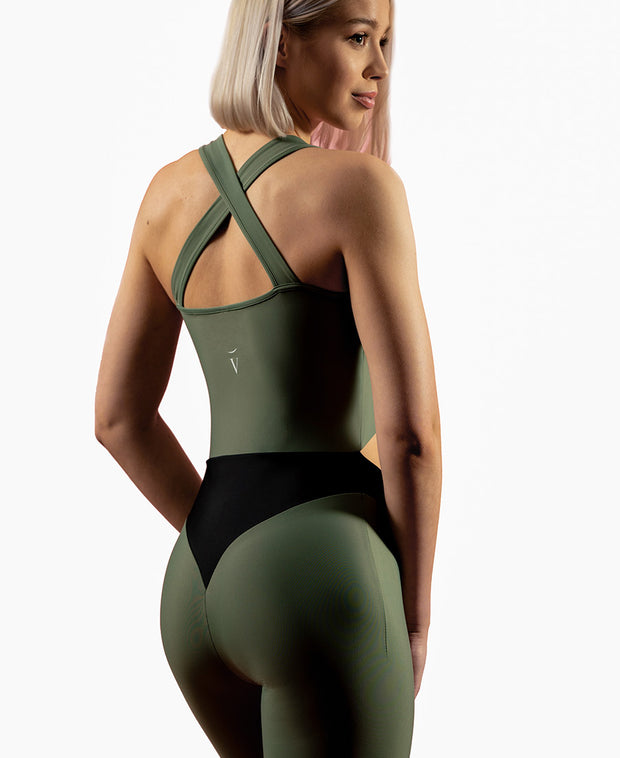 3/4 view of woman wearing olive green VanillaShanti one-piece yoga bodysuit or unitard