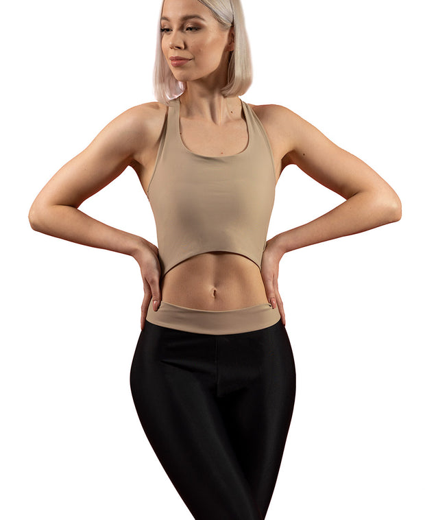 Front view of woman wearing sand VanillaShanti one-piece yoga bodysuit or unitard