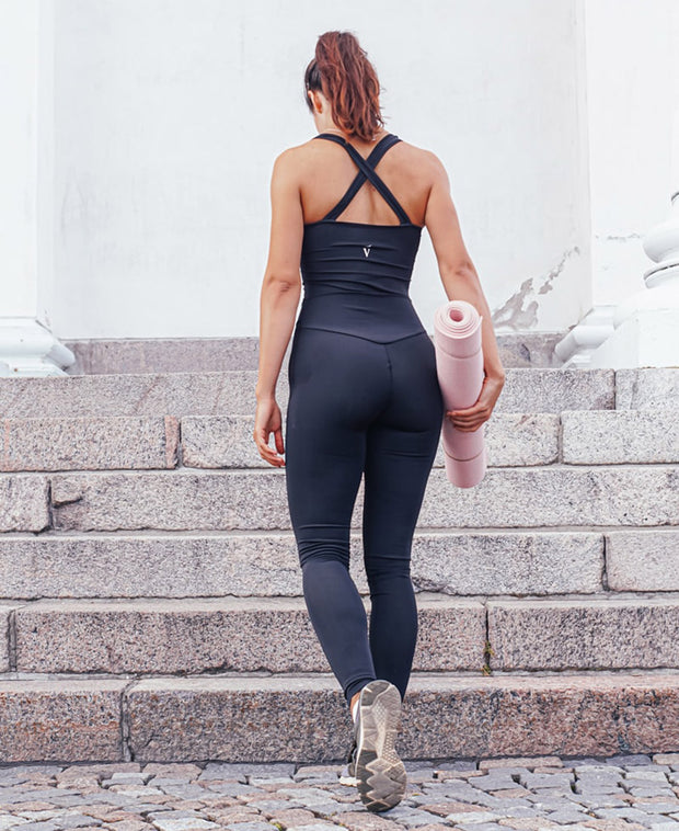 Back view of woman wearing black VanillaShanti one-piece yoga bodysuit or unitard