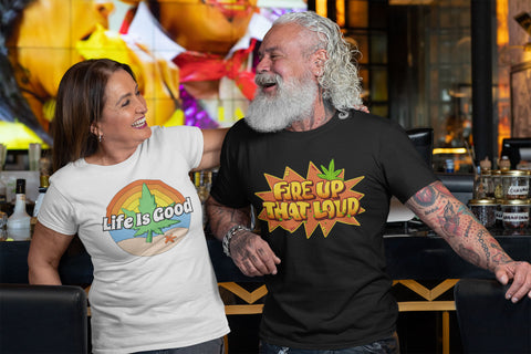 Man wearing a Fire Up That Loud T-Shirt and woman wearing a Life Is Good Cannabis T-Shirt - Magic Leaf Tees