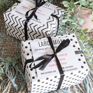 photo showing gift wrapped boxes, wrapped in black and white spotty and striped paper finished with ribbon tied in a bow