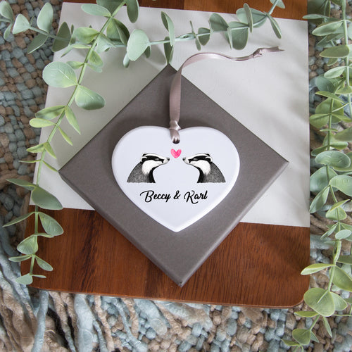 heart shaped white gloss polymer ornament with the badgers in love design, personalised with 2 names underneath, attached with ribbon to hang.