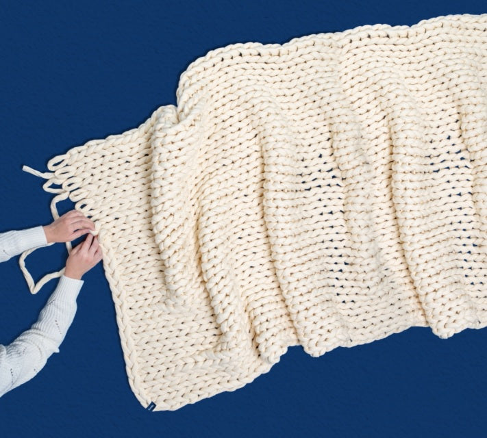 Someone hand knitting a white Bearaby weighted blanket, the Napper