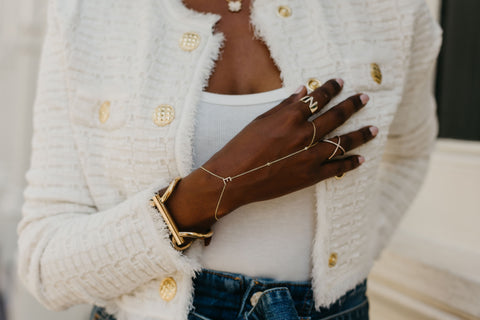 woman in white coat showing off gold and diamond jewelry