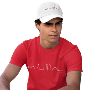 Male model wearing Doha Designs skyline t-shirt in red and skyline cap in white. Souvenirs of Qatar