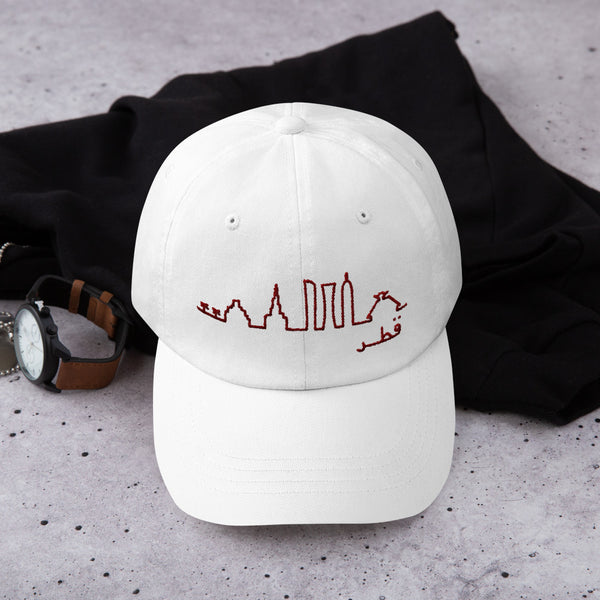 White cap with maroon embroidery of abstract Doha skyline