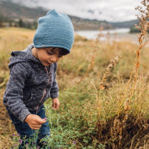 Young boy wearing Kéwkʷu hat in blue in grass field