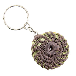 Pine needle pendant on a keychain, brown wrap on isolate white backdrop.