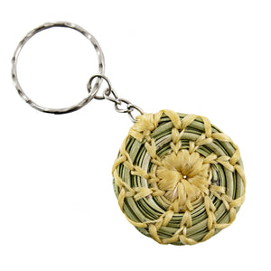 Pine needle pendant on a keychain, natural wrap on isolate white backdrop.