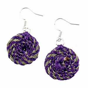 Two pine needle earrings with purple coloured twine on isolated white backdrop