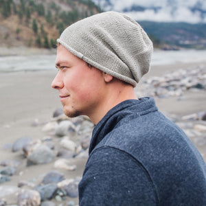 Sideview of man wearing Kéwkʷu slouch hat in sage colour on rocky beach