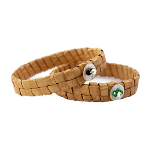 Two woven cedar bark bracelets on isolated white backdrop