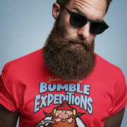 Bearded man with sunglasses wearing a Yukon Cornelius Bumble Expedition t-shirt from LlamaWrangler.com. Classic Christmas shirt inspired by the TV Classic Rudolph the Red Nosed Reindeer.