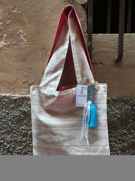 Bolso estampado plastificado con borla color celeste