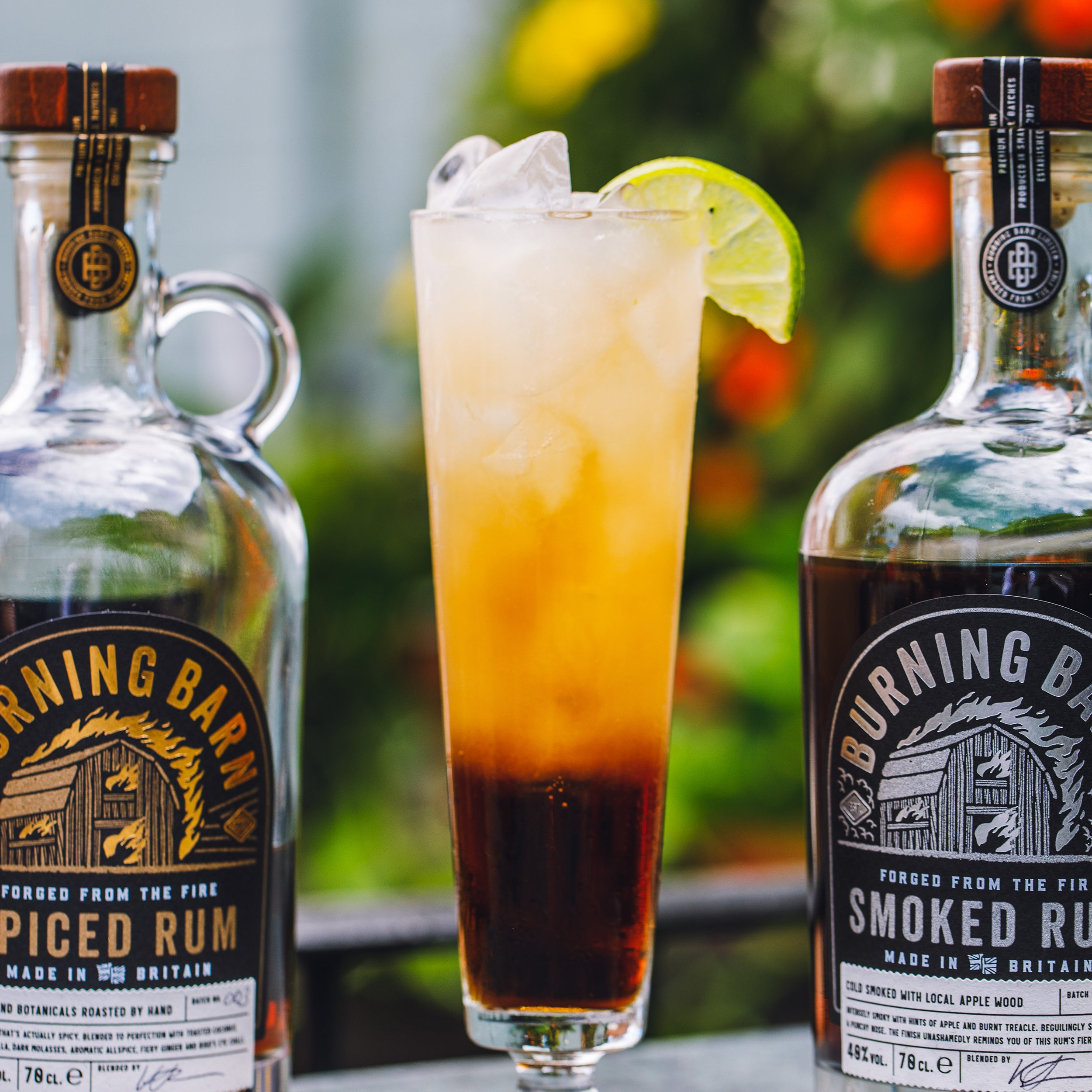 Burning Barn Iced Tea cocktail in tall glass, with rum bottles either side